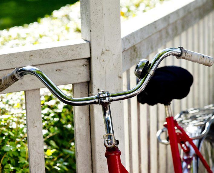 Röd cykel lutat mot staket